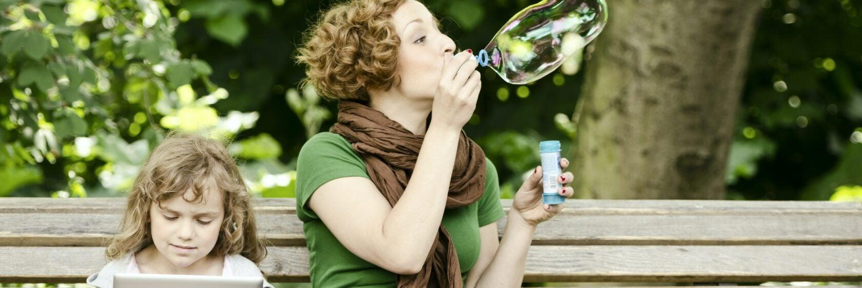 Frau mit Kind auf Parkbank Seifenblasen