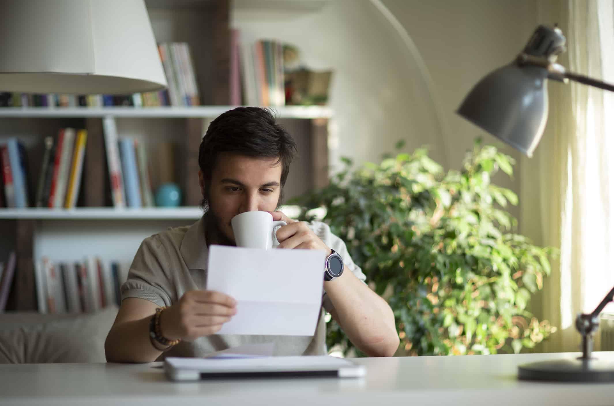 Mann trinkt Kaffee und schaut dabei auf ein Blatt Papier.