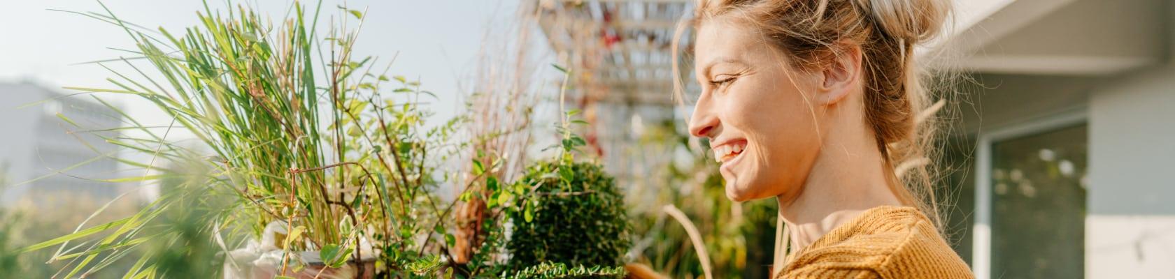 Frau kümmert sich gut gelaunt um die Pflanzen auf ihrem Balkon.