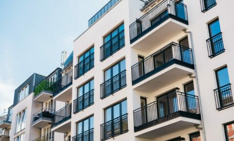Fassade eines Hauses mit mehreren Wohnungen und Balkonen.