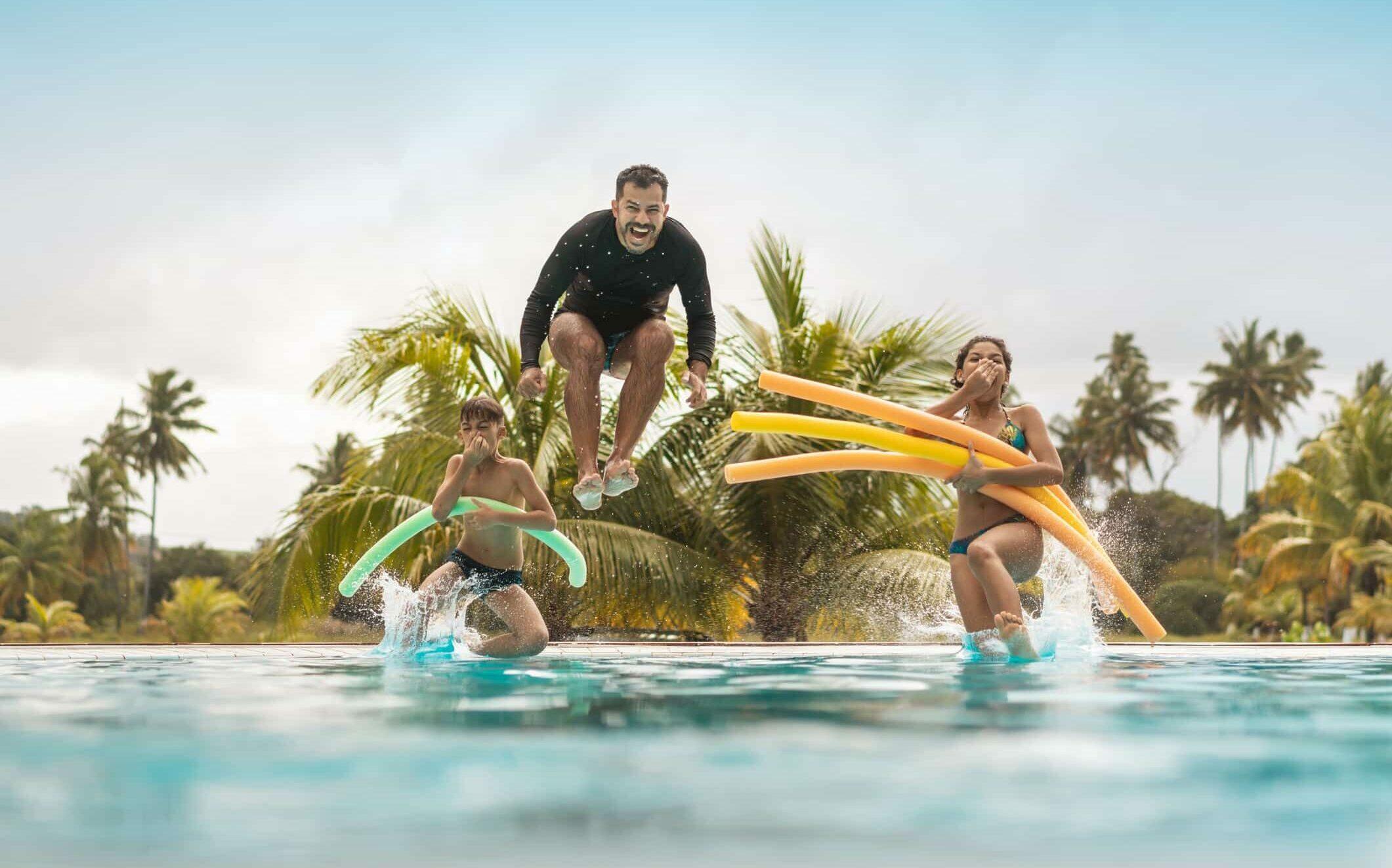 Personen mit Schwimmnudeln im Wasser, Palmen im Hintergrund.